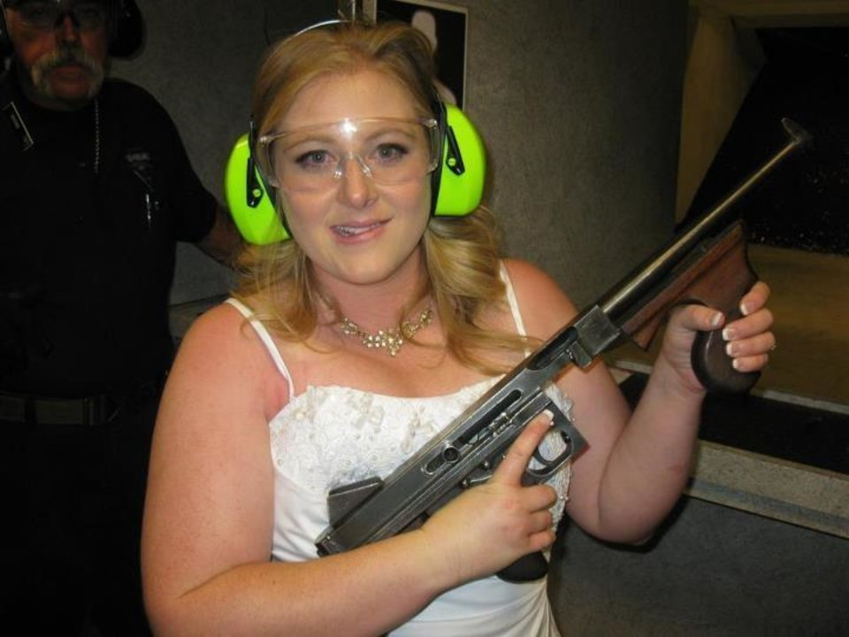 "This July 28, 2012 photo provided by Bob MacDuff shows Lindsae MacDuff holding an automatic weapon at the Gun store in Las Vegas after her ""shotgun wedding."" One Las Vegas shooting range is selling �take a shot at love� packages that include 50 submachine gun rounds. Another is offering wedding packages in which the bride and groom can pose with Uzis and ammunition belts. And a third invites lovebirds to renew their vows and shoot a paper cutout zombie in the face. (AP Photo/Bob MacDuff)"