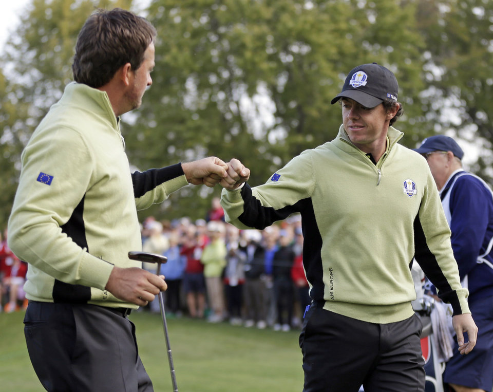 Photo -   Europe's Graeme McDowell and Rory McIlroy celebrate during a foursomes match at the Ryder Cup PGA golf tournament Friday, Sept. 28, 2012, at the Medinah Country Club in Medinah, Ill. (AP Photo/David J. Phillip)
