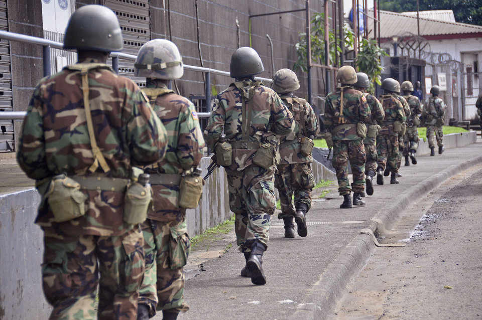Photo - Liberian soldiers walk through streets to prevent panic as fears of the deadly Ebola virus spread in the city of Monrovia, Liberia, Friday, Aug 1, 2014. U.S. health officials warned Americans not to travel to the three West African countries hit by the worst recorded Ebola outbreak in history. The travel advisory issued Thursday applies to nonessential travel to Guinea, Liberia and Sierra Leone, where the deadly disease has killed more than 700 people this year. (AP Photo/Abbas Dulleh)