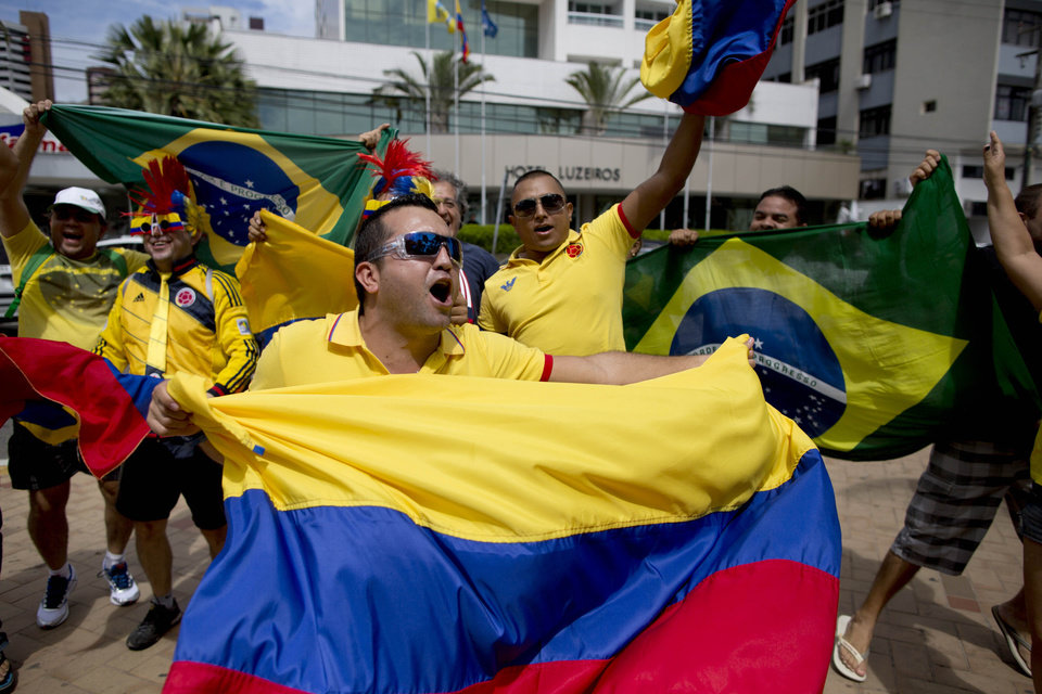 Photo - Fans of the Colombian national soccer team respond to television news cameras, waving their national flags, in front of the hotel where the Colombian national soccer team is staying in Fortaleza, Brazil, Thursday, July 3, 2014. Colombian supporters are in Fortaleza hoping to see some history being made in this northeastern World Cup city where Brazil and Colombia face off in the World Cup quarterfinals, Saturday. (AP Photo/Rodrigo Abd)