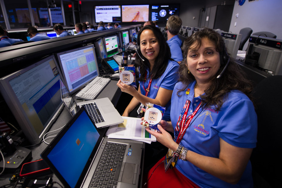 Photo -   In this photo released by NASA's JPL, Mars Science Laboratory (MSL) Pauline Hwang, left, and Nagin Cox pose for a photograph while holding packs given to each of the team members that contain a mars bar and peanuts in the Mission Support Area at JPL ahead of the planned landing of the Curiosity rover on Mars, Sunday, Aug. 5, 2012 in Pasadena, Calif. The MSL Rover named Curiosity was designed to assess whether Mars ever had an environment able to support small life forms called microbes. Curiosity is due to land on Mars at 10:31 p.m. PDT on Aug. 5, 2012 (1:31 a.m. EDT on Aug. 6, 2012). (AP Photo/NASA, Bill Ingalls)