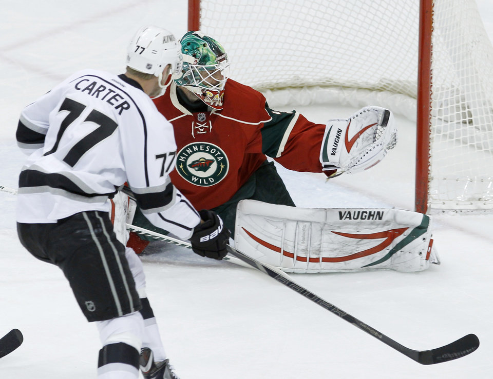Photo - Minnesota Wild goalie Niklas Backstrom (32), of Finland, stops a shot by Los Angeles Kings center Jeff Carter (77) during the first period of an NHL hockey game in St. Paul, Minn., Tuesday, April 23, 2013. (AP Photo/Ann Heisenfelt)
