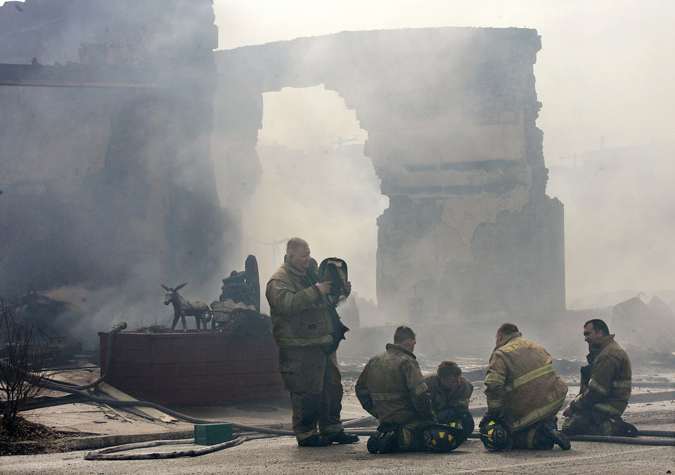 Photo - FIRE DAMAGE: Firefighters rest after bringing the worst part of the blaze under control. This is in front of the businesses. Firefighters from eight communities assisted  fire crews from Weleetka battle a large blaze that destroyed a block of downtown businesses. The fire ruined a floral shop, a popular restaurant and an embroidery store on Main Street in Weleetka Friday, March 6, 2009.  This photo was taken from the extended bucket of an Okmulgee Fire Department snorkel truck.  BY JIM BECKEL, THE OKLAHOMAN ORG XMIT: KOD