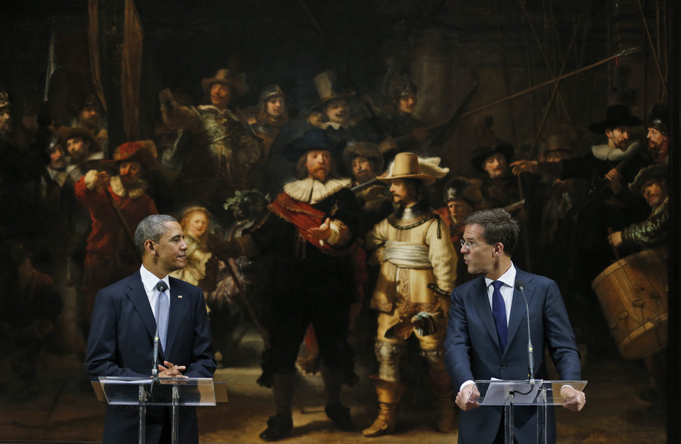 Photo - U.S. President Barack Obama, left, looks at Dutch Prime Minister Mark Rutte, right, in front of  Dutch master Rembrandt's The Night Watch painting during a visit to the Rijksmuseum in Amsterdam, Netherlands, Monday, March 24, 2014. Obama will attend the two-day Nuclear Security Summit in The Hague. (AP Photo/Jerry Lampen, POOL)
