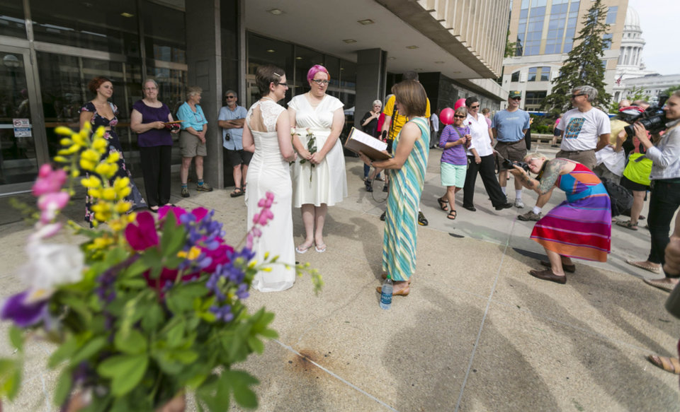 Photo - Officiant Tamara Packard, center, performs the marriage ceremony for Tina Cady, left, and Cody Huston Saturday, June 7, 2014, in Madison, Wis. On Friday a federal judge struck down the state's gay marriage ban. (AP Photo/Andy Manis)
