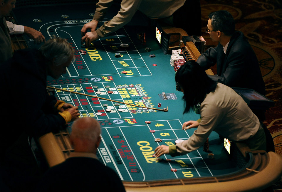 In this Sept. 18, 2013 photo, patrons play craps at a table at Mohegan Sun in Uncasville, Conn. As table games spread across the Northeast, resorts are using their own intelligence network more than ever to stay ahead of suspect players _ professional thieves as well as card counters _ who can easily hit multiple casinos in the span of a few days. (AP Photo/Jessica Hill)