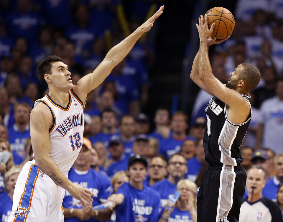 Photo - Oklahoma City's Steven Adams (12) defends as San Antonio's Tony Parker (9) shoots during Game 4 of the Western Conference Finals in the NBA playoffs between the Oklahoma City Thunder and the San Antonio Spurs at Chesapeake Energy Arena in Oklahoma City, Tuesday, May 27, 2014. Photo by Nate Billings, The Oklahoman