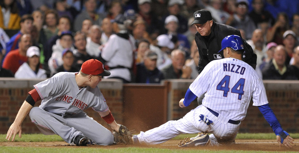 Cincinnati Reds third baseman Todd Frazier, left, tags out Chicago Cubs\' Anthony Rizzo at third base in the fourth inning during a baseball game in Chicago, Thursday, Aug. 9, 2012. (AP Photo/Paul Beaty)