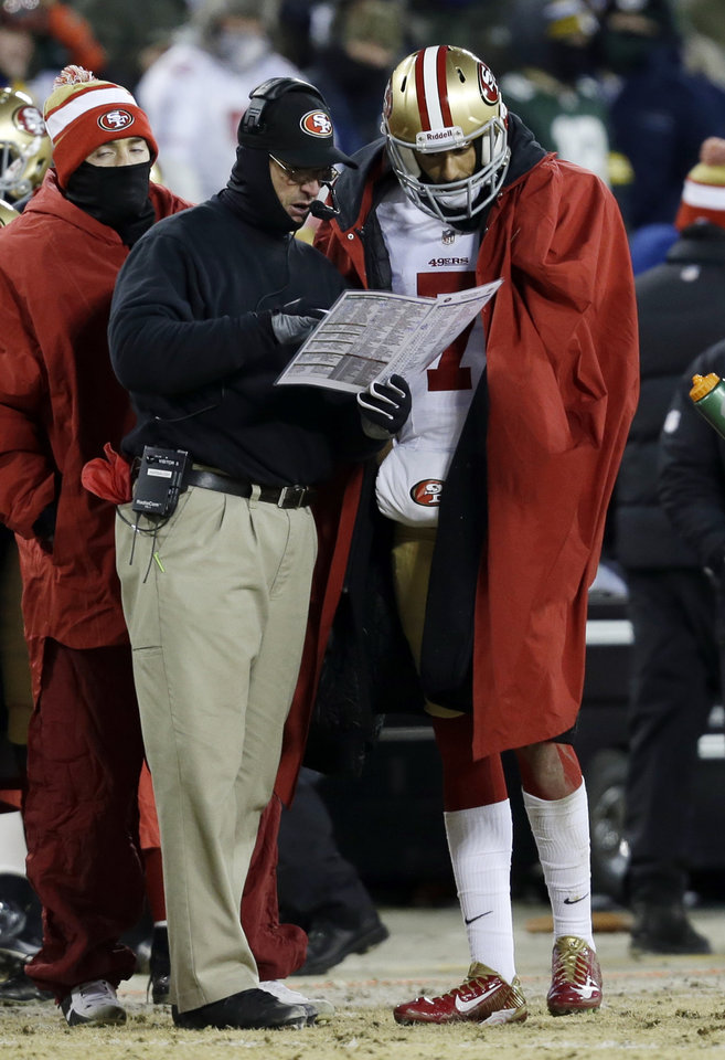 Photo - San Francisco 49ers head coach Jim Harbaugh talks to the 49ers quarterback Colin Kaepernick (7) during a time out in the first half of an NFL wild-card playoff football game, Sunday, Jan. 5, 2014, in Green Bay, Wis. (AP Photo/Mike Roemer)