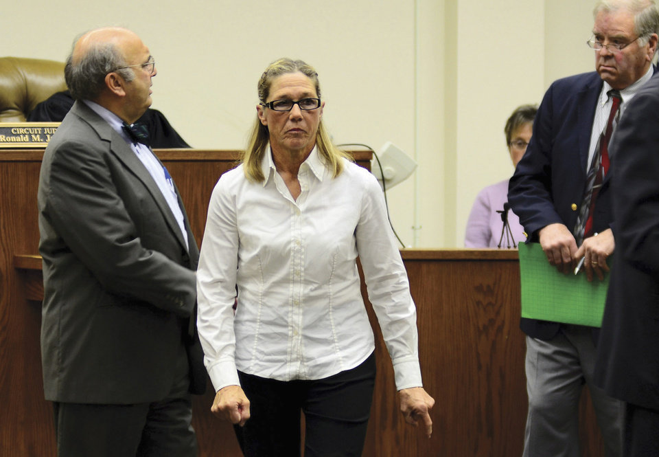 Photo -   FILE - In this Oct. 22, 2012 file photo, former Dixon, Ill., comptroller Rita Crundwell leaves a courtroom in Dixon with her attorney Paul Gaziano, left, after making her first appearance in the northern Illinois city to face charges she siphoned millions of dollars in public funds into a secret bank account. On Wednesday, Nov. 14, 2012, Crundwell is expected to plead guilty at federal court in Rockford, Ill., to stealing $53 million to fund a lavish lifestyle while overseeing the public finances of the city of Dixon. (AP Photo/Sauk Valley Media, Alex T. Paschal, File)