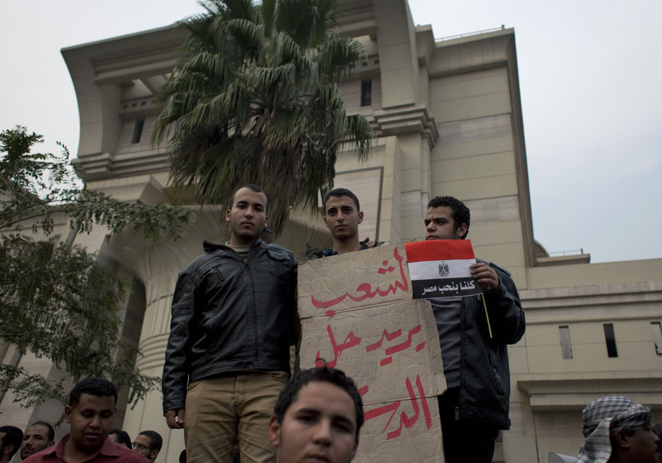 Photo - Supporters of Egyptian President Mohammed Morsi hold a placard with Arabic that reads,