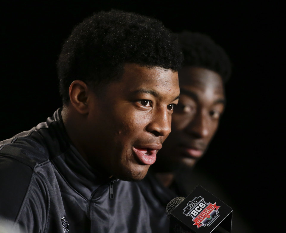 Photo - Florida State wide receiver Kenny Shaw, right, looks over as quarterback Jameis Winston answers questions during a news conference on Friday, Jan. 3, 2014 in Newport Beach, Calif. Florida State is scheduled to play Auburn on Monday, in the BCS national championship NCAA college football game. (AP Photo/Chris Carlson)