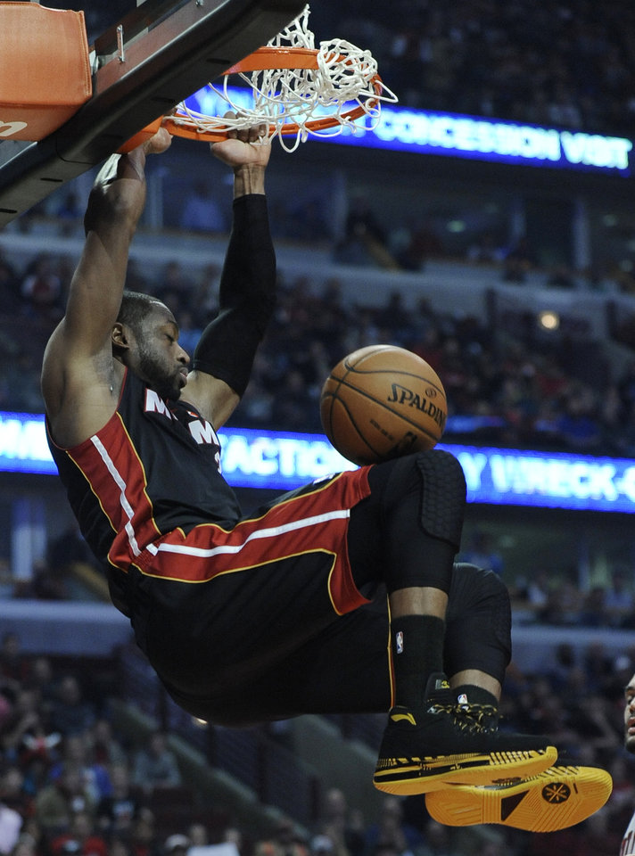 Photo - Miami Heat's Dwyane Wade dunks during the first quarter of an NBA basketball game against the Chicago Bulls in Chicago, Sunday, March 9, 2014. (AP Photo/ Paul Beaty)