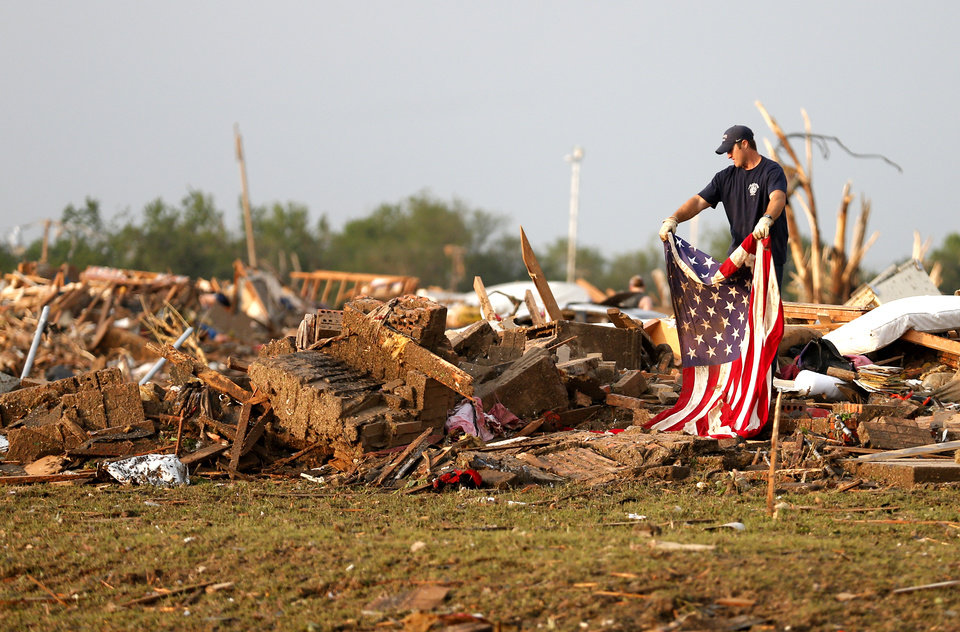 Todd Hinkle  with the Stillwater firefighter local 2095 run rolls an American Flag on a destroyed home in a residential area near the off Telephone Road in Moore following a deadly tornado, Monday, May 20, 2013. Photo by Sarah Phipps, The Oklahoman