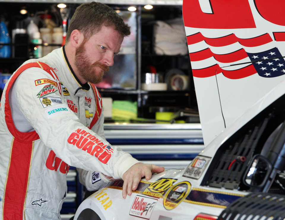 Photo - Driver Dale Earnhardt Jr. checks his car during a break in practice for Sunday's NASCAR Sprint Cup series auto race at New Hampshire Motor Speedway, Friday, July 11, 2014, in Loudon, N.H. (AP Photo/Jim Cole)