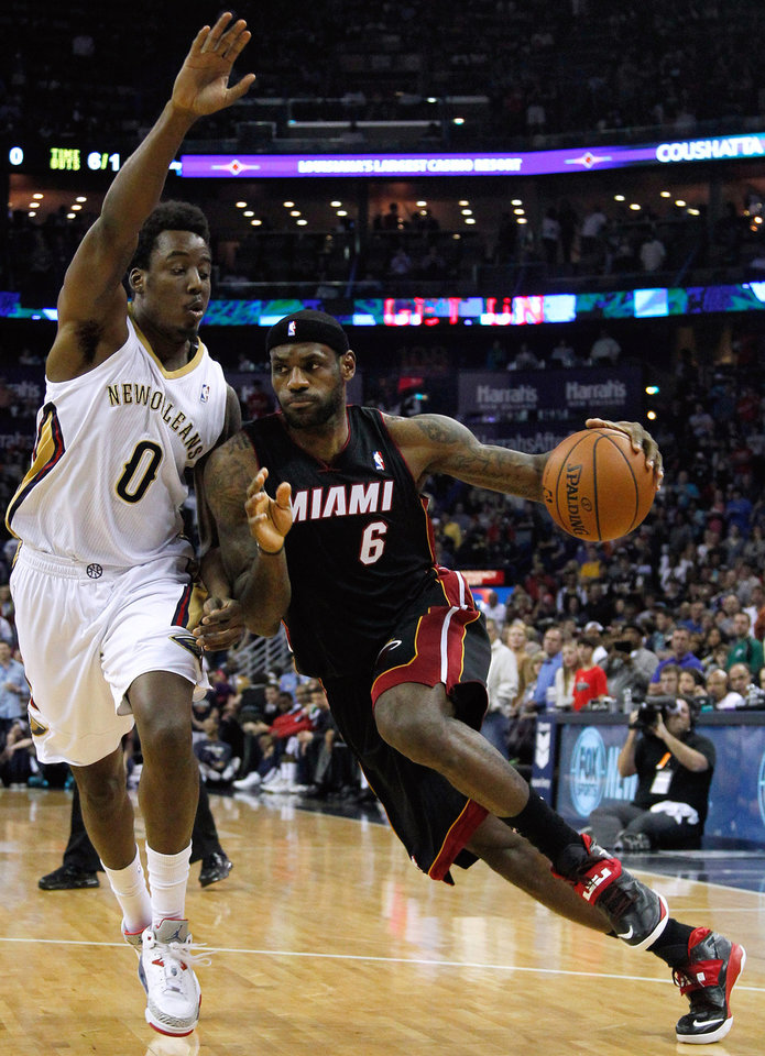 Photo - Miami Heat forward LeBron James (6) drives against New Orleans Pelicans forward Al-Farouq Aminu (0) during the first half of an NBA basketball game in New Orleans, Saturday, March 22, 2014. (AP Photo/Jonathan Bachman)