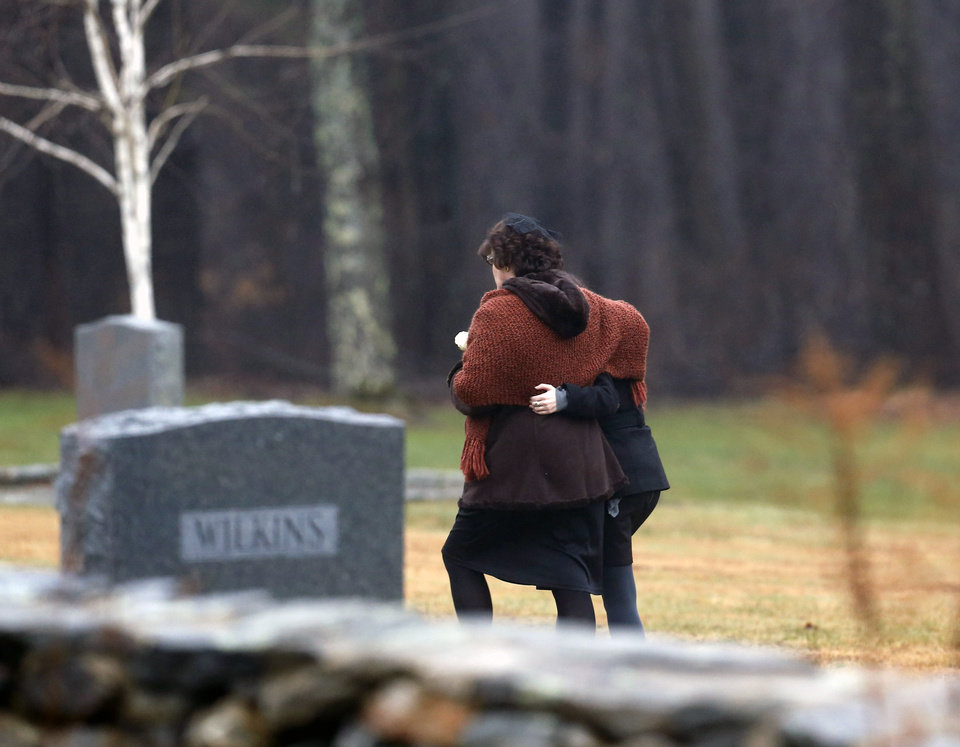 Photo - Veronique Pozner, left, embraces a young girl as she arrives at B'nai Israel Cemetery for burial services for her 6-year-old son Noah Pozner, Monday, Dec. 17, 2012, in Monroe, Conn. Noah Pozner was killed when Adam Lanza walked into Sandy Hook Elementary School in Newtown, Conn., Friday and opened fire, killing 26 people, including 20 children, before killing himself. (AP Photo/Julio Cortez)
