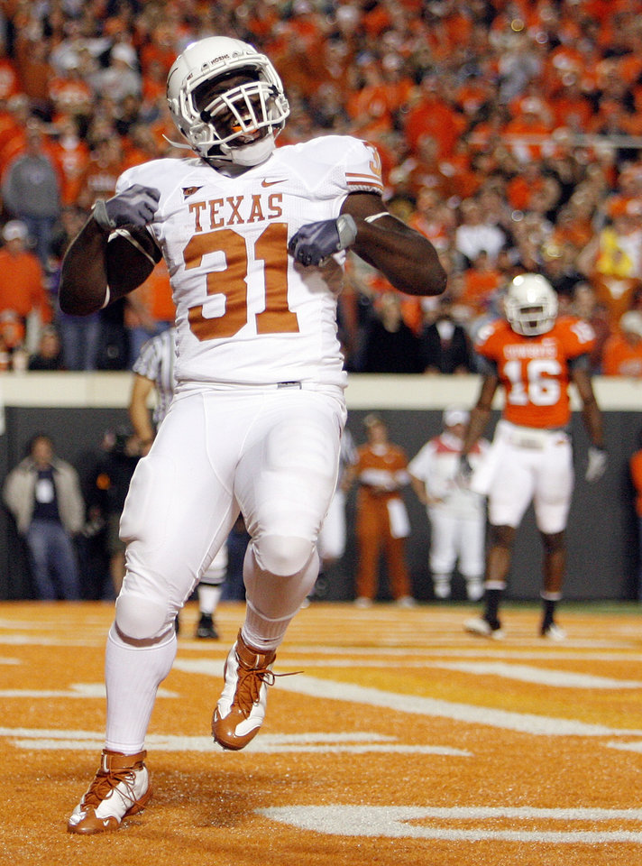 Photo - Cody Johnson (31) of Texas celebrates after rushing for a touchdown during the college football game between the Oklahoma State University Cowboys (OSU) and the University of Texas Longhorns (UT) at Boone Pickens Stadium in Stillwater, Okla., Saturday, Oct. 31, 2009. OSU's Perrish Cox (16) is in the background. Texas won, 41-14. Photo by Nate Billings, The Oklahoman