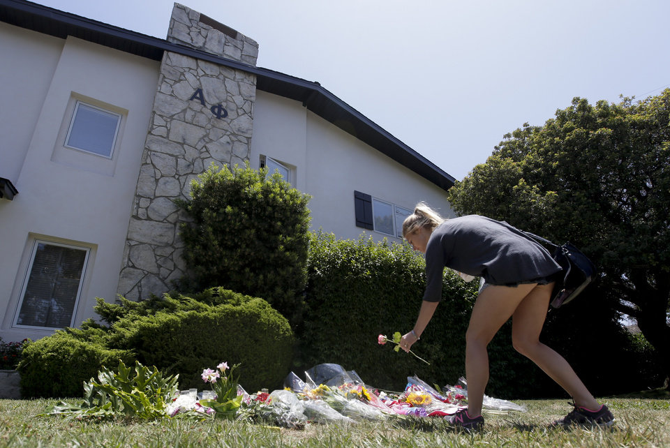 Photo - A woman puts down a flower on a makeshift memorial at the Alpha Phi sorority house where two women were killed as part of Friday night's mass shooting Sunday, May 25, 2014 in the Isla Vista area near Goleta, Calif.   Sheriff's officials said Elliot Rodger, 22, went on a rampage near the University of California, Santa Barbara, stabbing three people to death at his apartment before shooting and killing three more in a crime spree through a nearby neighborhood.(AP Photo/Chris Carlson)