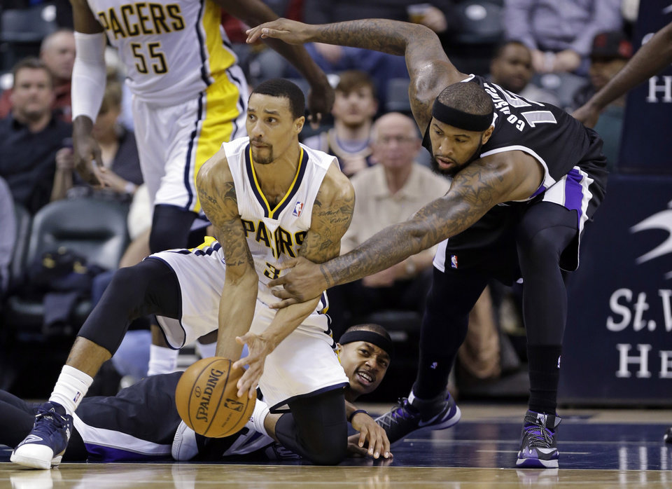 Photo - Indiana Pacers guard George Hill, left, tries to makes a pass after picking up a loose ball in front of Sacramento Kings guard Isaiah Thomas, center, as center DeMarcus Cousins reaches for the ball in the first half of an NBA basketball game in Indianapolis, Tuesday, Jan. 14, 2014.  (AP Photo/Michael Conroy)