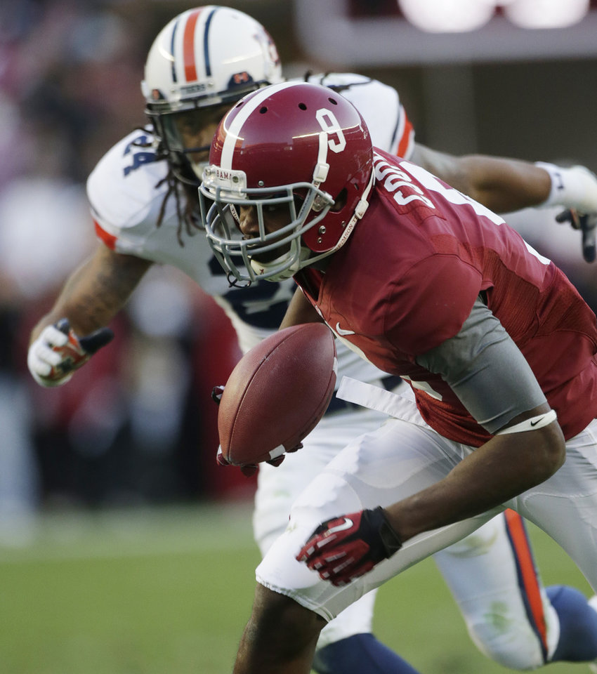 Photo -   Alabama wide receiver Amari Cooper (9) catches a 29-yard touchdown pass as Auburn defensive back Ryan Smith (24) pursues during the first half of a NCAA college football game at Bryant-Denny Stadium in Tuscaloosa, Ala., Saturday, Nov. 24, 2012. (AP Photo/Dave Martin)