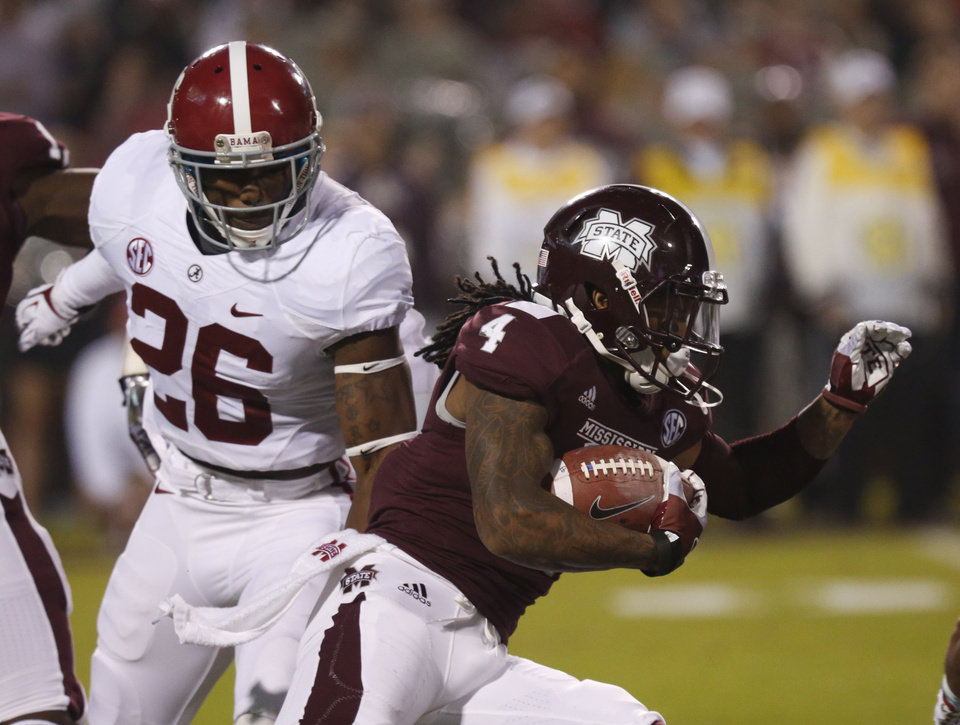 Photo - Mississippi State's Jameon Lewis (4) runs back a punt past Alabama's Landon Collins (26) during the first half of an NCAA college football game, Saturday, Nov. 16, 2013, in Starkville, Miss. (AP Photo/Rogelio Solis)