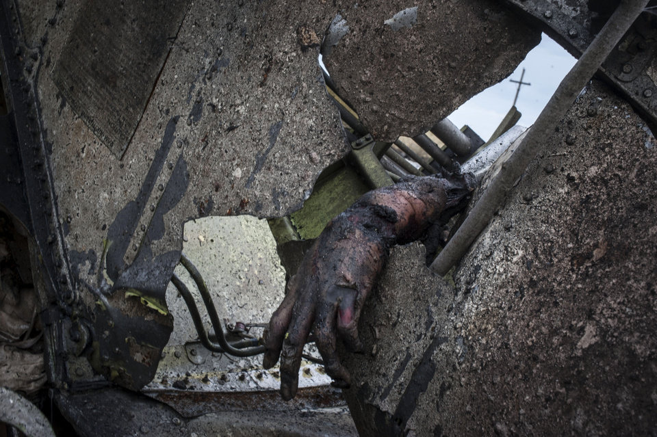 Photo - EDS NOTE: GRAPHIC CONTENT - The hand of victim lies among the wreckage of the crashed Malaysia Airlines Flight 17 lies near the village of Hrabove, eastern Ukraine, Saturday, July 19, 2014. World leaders demanded Friday that pro-Russia rebels who control the eastern Ukraine crash site of Malaysia Airlines Flight 17 give immediate, unfettered access to independent investigators to determine who shot down the plane. (AP Photo/Evgeniy Maloletka)