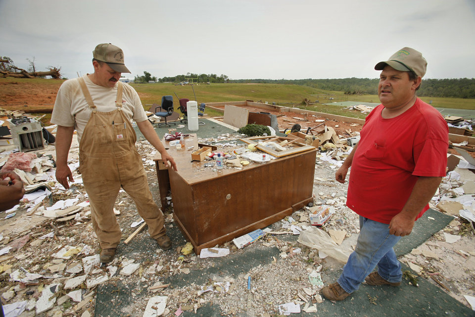 Photo - Cousins Glenn and Mike Rosenfelt marvel at a desk that remained intact and in its original location on Wednesday, May 12, 2010, in Little Axe, Okla.  The rest of the administration building at Little Axe School was blown away by Monday's severe storms.  Photo by Steve Sisney, The Oklahoman