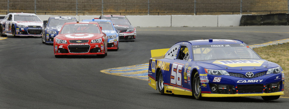 Photo - Martin Truex Jr. (56) leads Juan Pablo Montoya as they race during the NASCAR Sprint Cup Series auto race Sunday, June 23, 2013, in Sonoma, Calif. (AP Photo/Ben Margot)