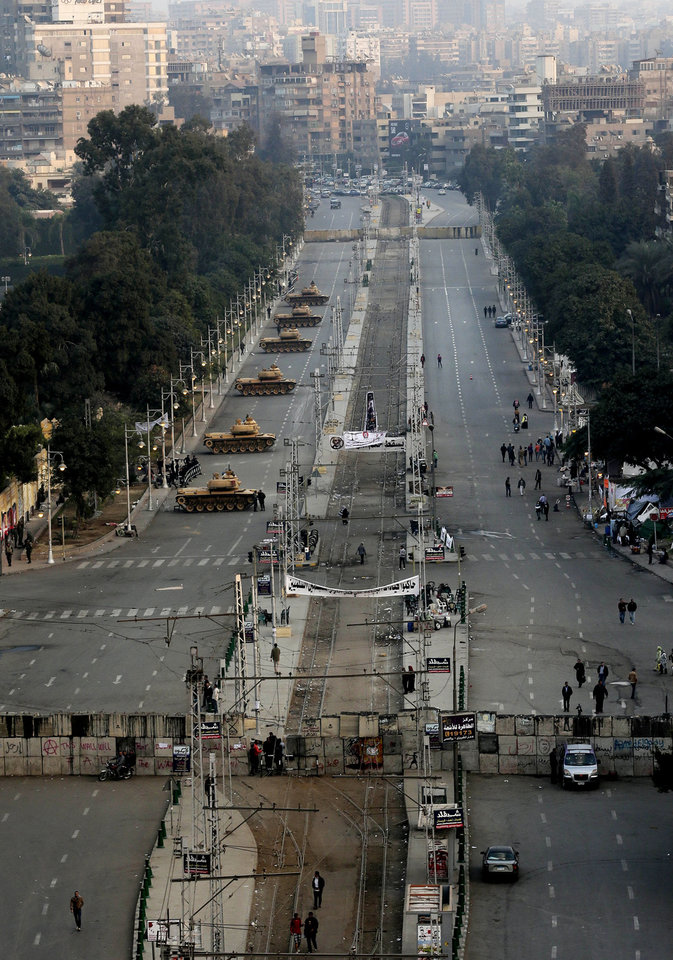 """Photo - Military tanks deployed in front of the presidential palace in Cairo, Egypt, Sunday, Dec. 16, 2012. Key Egyptian rights groups called Sunday for a repeat of the first round of the constitutional referendum, alleging the vote was marred by widespread violations. Islamists who back the disputed charter claimed they were in the lead with a majority of """"yes"""" votes. (AP Photo/Hassan Ammar)"""