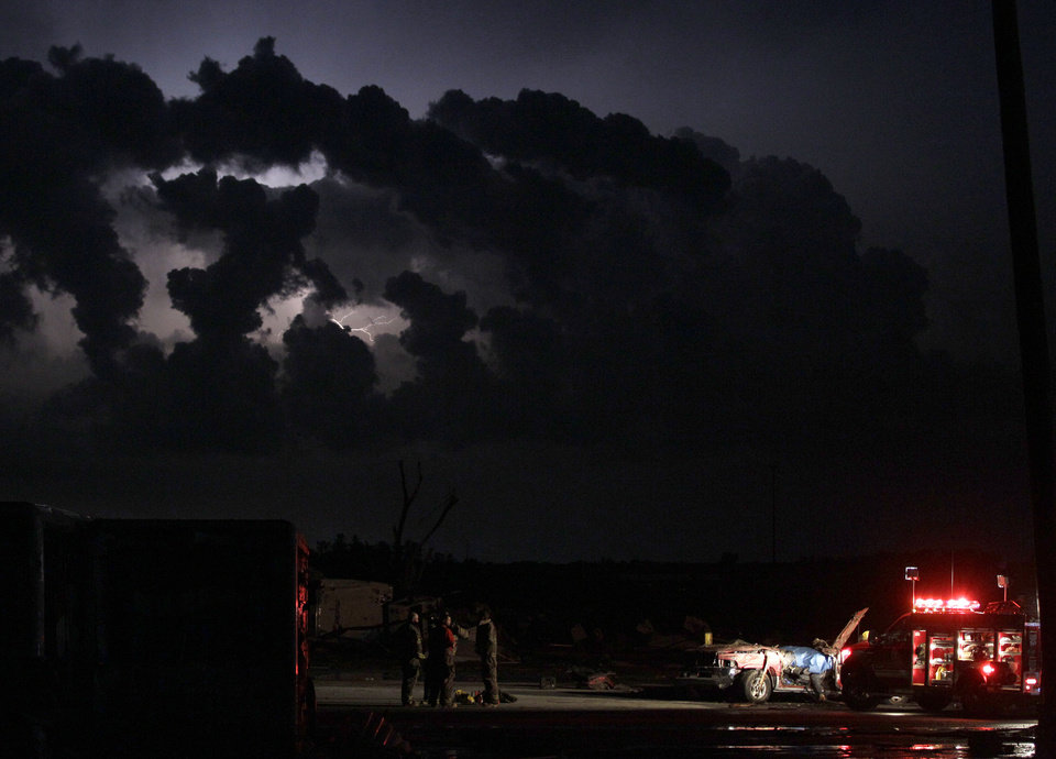 Photo - Emergency workers wait for a medical team after finding a body in a tornado ravaged car in Joplin, Mo., Monday, May 22, 2011. A large tornado moved through much of the city Sunday, damaging a hospital and hundreds of homes and businesses. (AP Photo/Charlie Riedel) ORG XMIT: MOCR104