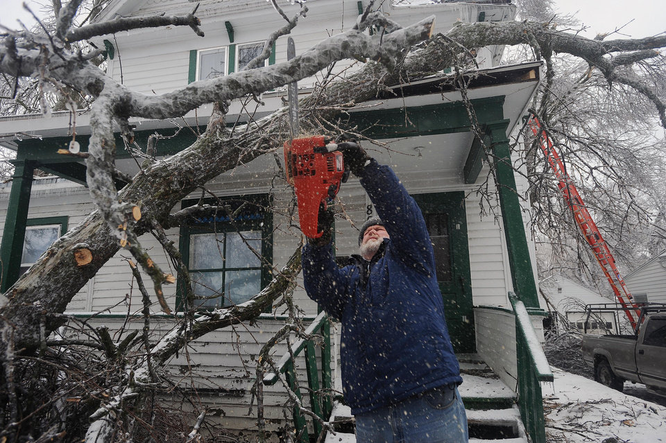 Photo - Tom Jandl removes branches from a fallen tree on his rental property at the corner of 13th Street and Prairie Avenue Wednesday, April 10, 2013 in Sioux Falls, S.D. (AP Photo/Argus Leader, Jay Pickthorn) NO SALES