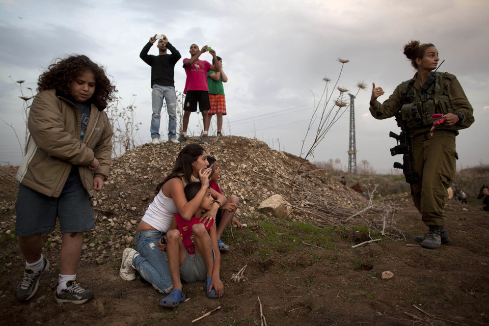 Israelis take cover as an air raid siren warns of incoming rockets from Gaza as Iron Dome missile is launched in Tel Aviv, to intercept a rocket fired from Gaza, Saturday, Nov. 17, 2012. Israel bombarded the Hamas-ruled Gaza Strip with nearly 200 airstrikes early Saturday, the military said, widening a blistering assault on Gaza rocket operations to include the prime minister's headquarters, a police compound and a vast network of smuggling tunnels. (AP Photo/Oded Balilty)