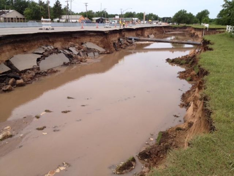 Portion on roadway and a large section of the dirt has been washed away, creating a canyon about 12 feet deep on north side of NE 23,just west of Air Depot. The road is open, but traffic in the area is restricted to one lane each direction. Photo by Jim Beckel