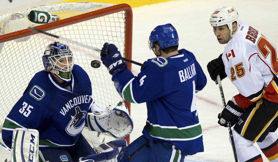 From left, Vancouver Canucks goalie Cory Schneider, Keith Ballard and Calgary Flames\' Steve Begin watch the puck after Schneider made a save during the second period of their NHL hockey game, Wednesday, Jan. 23, 2013, in Vancouver, British Columbia. (AP Photo/The Canadian Press, Darryl Dyck)