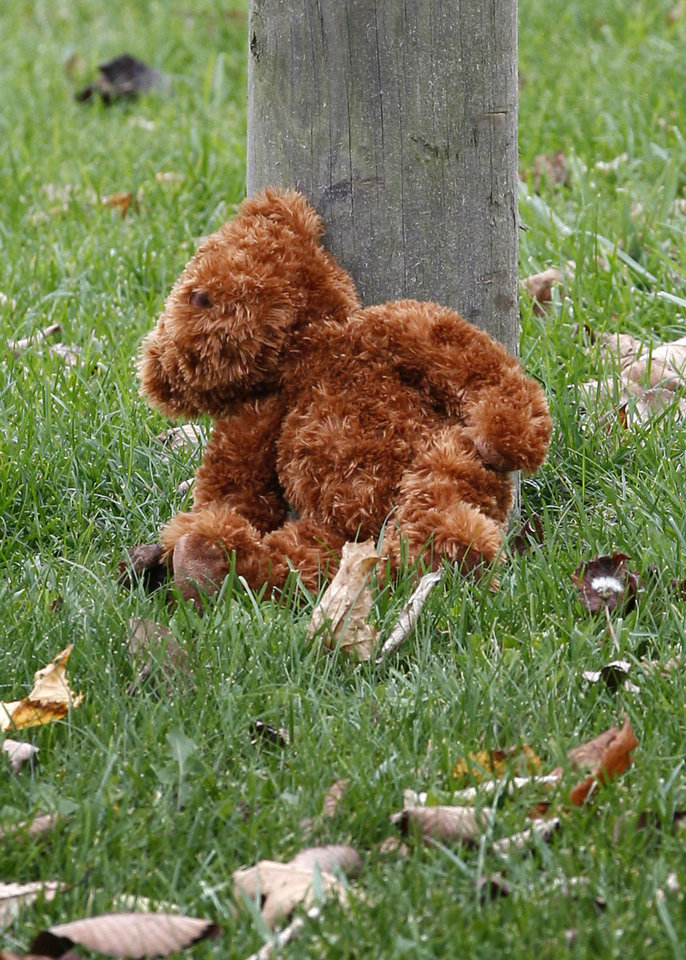 Photo -   A teddy bear rests at the post of a sign near the entrance to the parking lots for the Pittsburgh Zoo and PPG Aquarium on Monday, Nov. 5, 2012, in Pittsburgh. Zoo officials said a young boy was killed after he fell into the exhibit that was home to a pack of African painted dogs who pounced on the boy and mauled him on Sunday, Nov. 4, 2012. (AP Photo/Keith Srakocic)