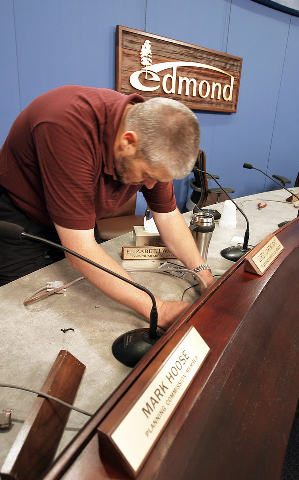 Photo - Kevin Carr, Edmond's director of Information Technology, installs the new voting machine in city council chambers. The equipment is expected to be working for Monday's council meeting. PHOTO BY DAVID MCDANIEL, THE OKLAHOMAN