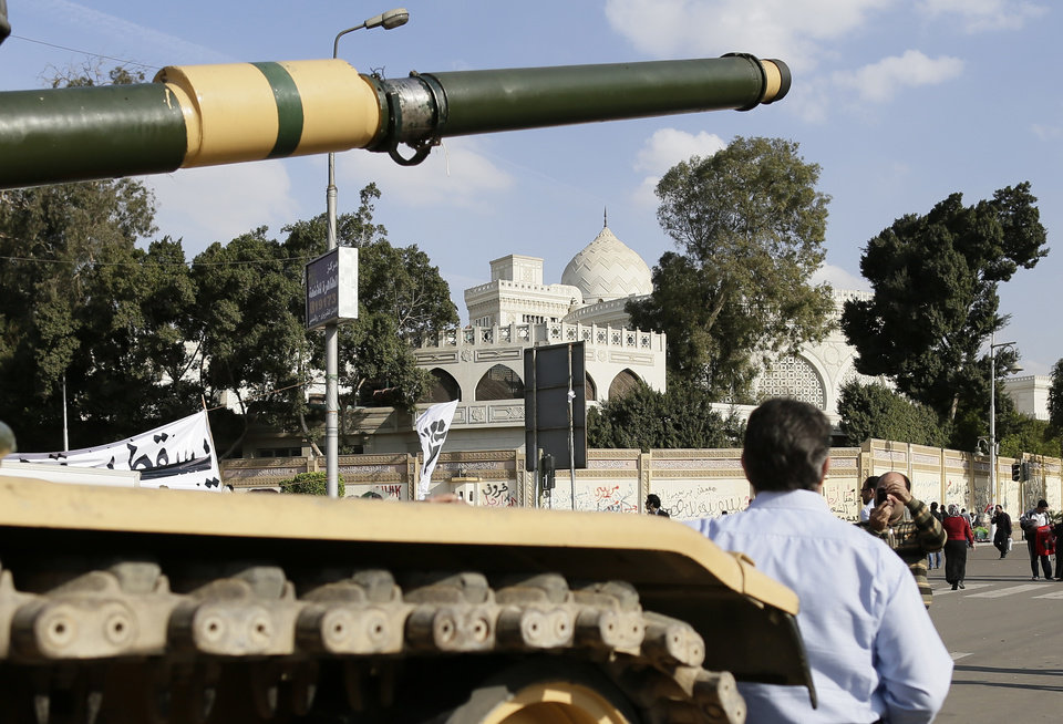 An Egyptian protester takes a picture with his mobile of another in front of an Egyptian army tank outside the presidential palace, background, in Cairo, Egypt, Saturday, Dec. 8, 2012. Egypt\'s military has warned of \'disastrous consequences\' if the political crisis gripping the country is not resolved through dialogue. (AP Photo/Hassan Ammar)