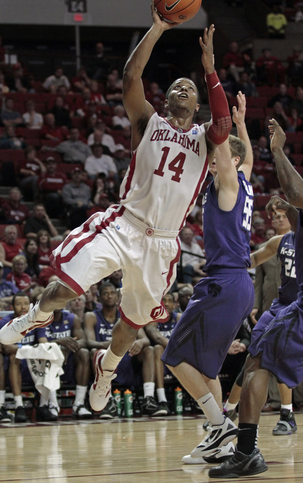 Photo - Carl Blair shoots under the bucket past Kansas State Wildcats' Will Spradling (55) in the first half as the University of Oklahoma (OU) Sooners play the Kansas State Wildcats in men's college basketball at the Lloyd Noble Center on Saturday, Jan. 14, 2012, in Norman, Okla.  Photo by Steve Sisney, The Oklahoman