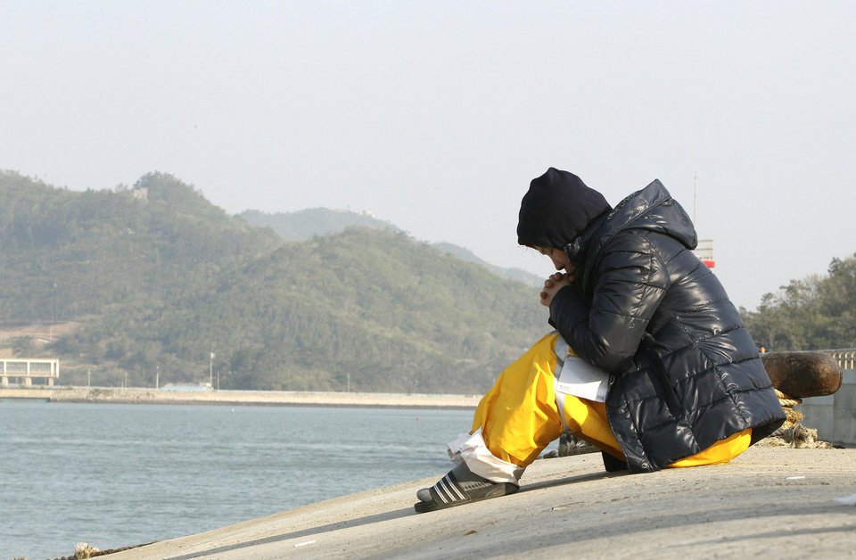 Photo - A relative of a passenger aboard the sunken ferry Sewol prays as she waita for her missing loved one at a port in Jindo, South Korea, Monday, April 21, 2014. Divers continued the grim work of recovering bodies from inside the sunken South Korean ferry Monday, securing a new entryway into the wreck, as a newly released transcript showed the ship was crippled by confusion and indecision well after it began listing. The transcript suggests that the chaos may have added to a death toll that could eventually exceed 300. (AP Photo/Ahn Young-joon)