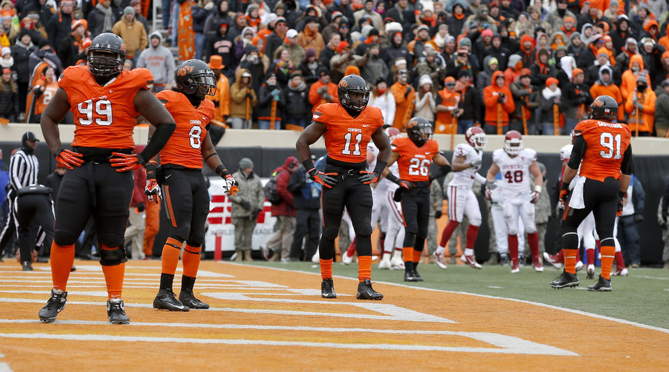 Photo - The OSU defense looks towards the bench after OU scored a touchdown in the final minute of the Bedlam college football game between the Oklahoma State University Cowboys (OSU) and the University of Oklahoma Sooners (OU) at Boone Pickens Stadium in Stillwater, Okla., Saturday, Dec. 7, 2013. Oklahoma won 33-24. Photo by Bryan Terry, The Oklahoman