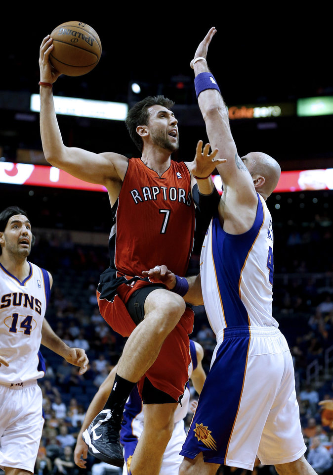 Photo - Toronto Raptors' Andrea Bargnani (7), of Italy, shoots over Phoenix Suns' Marcin Gortat, of Poland, during the first half of an NBA basketball game, Wednesday, March 6, 2013, in Phoenix. (AP Photo/Matt York)
