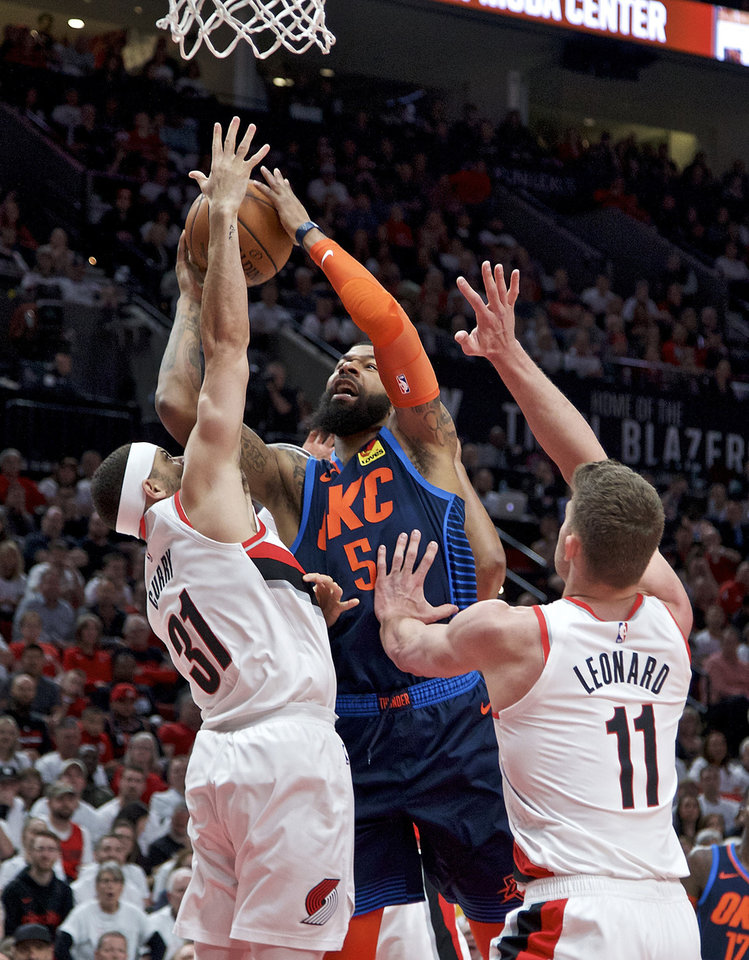 Photo - Oklahoma City Thunder forward Markieff Morris, center, shoots over Portland Trail Blazers guard Seth Curry, left, and forward Meyers Leonard during the first half of Game 5 of an NBA basketball first-round playoff series, Tuesday, April 23, 2019, in Portland, Ore. (AP Photo/Craig Mitchelldyer)