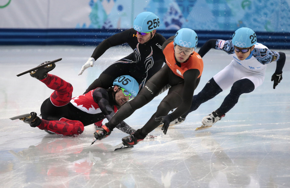 Photo - Charles Hamelin of Canada, left, crashes out with Eduardo Alvarez of the United States, second from left, as they compete with Sjinkie Knegt of Netherlands, second from right, and Victor An of Russia in a men's 1000m short track speedskating quarterfinal at the Iceberg Skating Palace during the 2014 Winter Olympics, Saturday, Feb. 15, 2014, in Sochi, Russia. (AP Photo/Ivan Sekretarev)