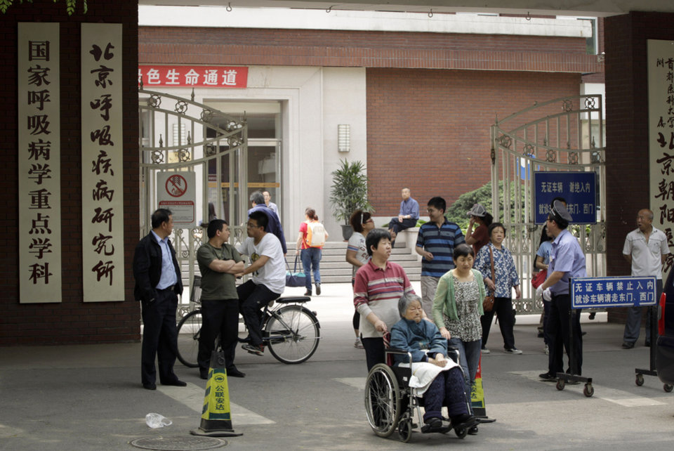 Photo -   People enter and exit the hospital where Chinese legal activist Chen Guangcheng was taken to receive medical care in Beijing, Monday, May 7, 2012. Chen, a symbol in China's civil rights movement, may be able to leave to study in the United States under still-evolving arrangements announced Friday, May 4, 2012, by Washington and Beijing to end a weeklong diplomatic standoff over his case. (AP Photo/Vincent Thian)