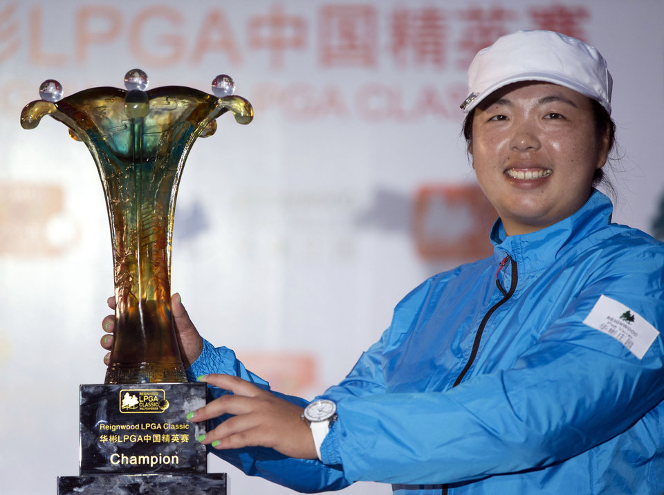 Photo - China's Feng Shanshan touches her trophy after winning the Reignwood LPGA Classic golf tournament at Pine Valley Golf Club on the outskirts of Beijing, China, Sunday, Oct. 6, 2013. (AP Photo/Alexander F. Yuan)