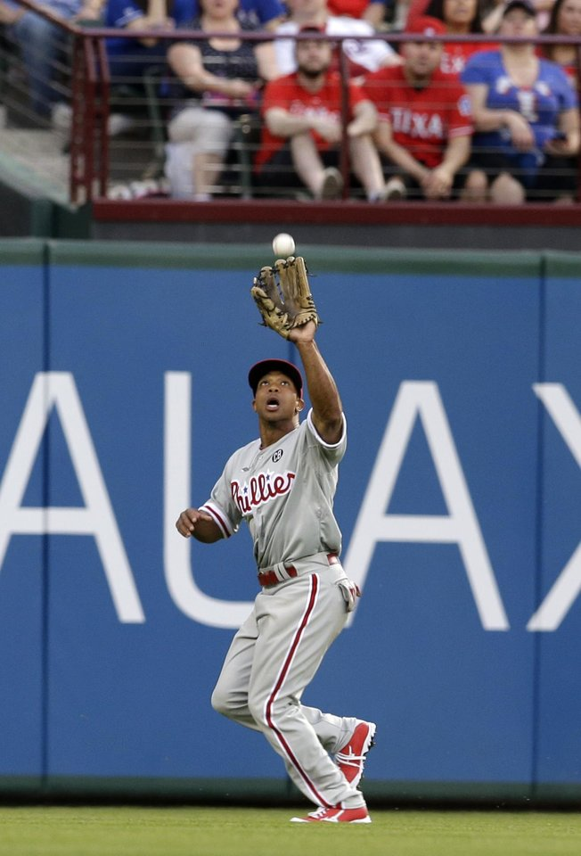 Photo - Philadelphia Phillies center fielder Ben Revere reaches up to grab a fly-out by Texas Rangers' Prince Fielder in the first inning of a baseball game, Tuesday, April 1, 2014, in Arlington, Texas. (AP Photo/Tony Gutierrez)