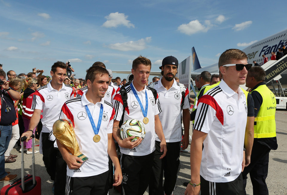 Photo - German national soccer players from left :  Miroslav Klose, Philipp Lahm, Lars Bender, Sami Khedira and Toni Kroos arrive with the team  at Tegel airport in Berlin Tuesday July 15, 2014.  Germany beat Argentina 1-0 on Sunday to win its fourth World Cup title. (AP Photo/Karina Hessland,pool)