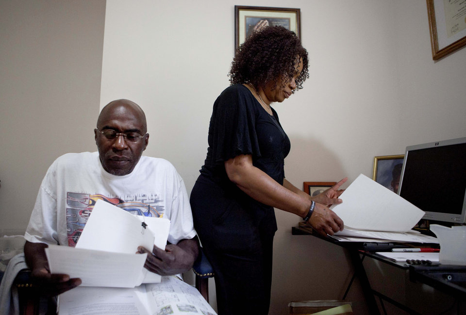 Photo -   Michael, left, and Patricia Jackson sift through bank documents in their home Saturday, June 16, 2012, in Marietta, Ga. On a suburban cul-de-sac northwest of Atlanta, the Jacksons are struggling to keep a house worth $100,000 less than they owe. Their voices and those of many others tell the story of a country that, for all the economic turmoil of the past few years, continues to believe things will get better. But until it does, families are trying to hang on to what they've got left. The Great Recession claimed nearly 40 percent of Americans' wealth, the Federal Reserve reported last week. The new figures, showing Americans' net worth has plunged back to what it was in 1992, left economists shuddering. (AP Photo/David Goldman)