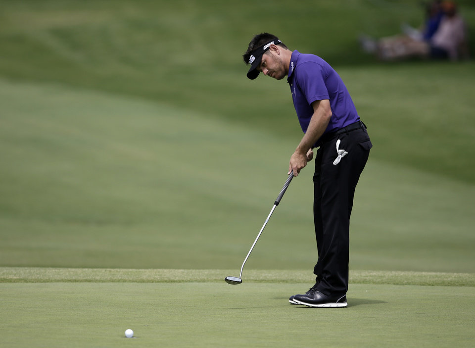 Photo - Louis Oosthuizen, of South Africa, sinks a birdie putt on the 15th green during the third round of the Byron Nelson Championship golf tournament, Saturday, May 17, 2014, in Irving, Texas. Oosthuizen finished the round at 10 under par. (AP Photo/Tony Gutierrez)